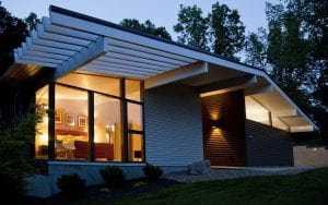 modern home with retro touches and Hardie plank siding at night