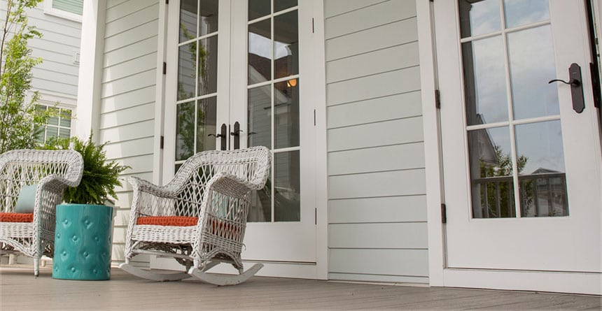 Front porch with white rocking chairs, double french doors, and James Hardie siding.